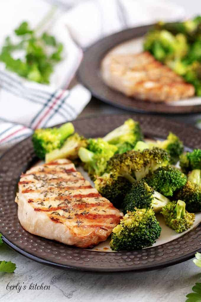 Two plates of grilled pork chops served with the broccoli.