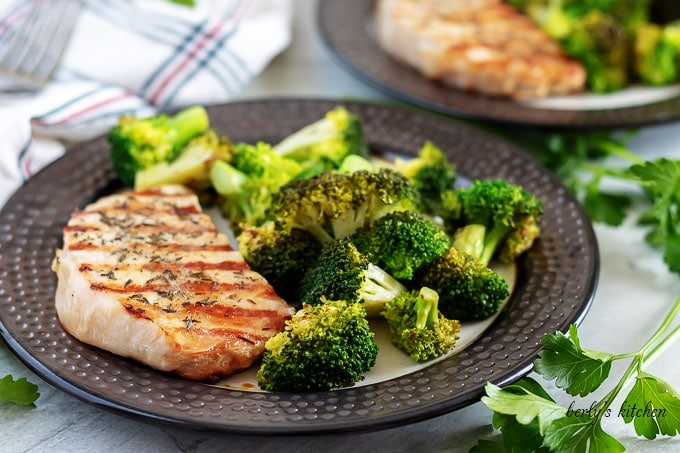 A grilled pork chop, on a plate, with a side of broccoli.