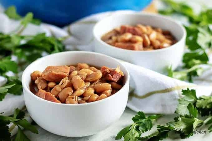 Two bowls of ham and beans garnished with fresh parsley.