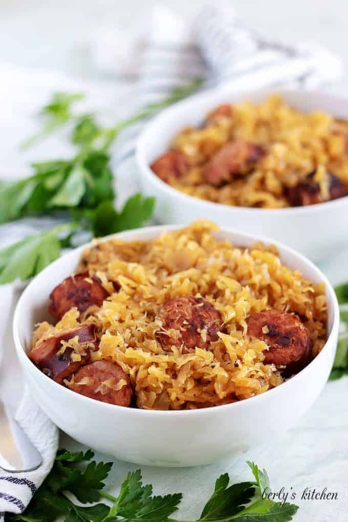 The finished kielbasa and sauerkraut served in two bowls with parsley.