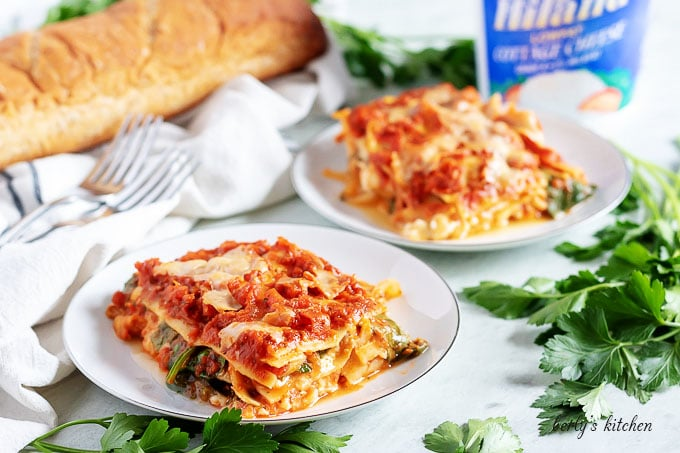 Two pieces of mushroom lasagna on with plates garnished with parsley.
