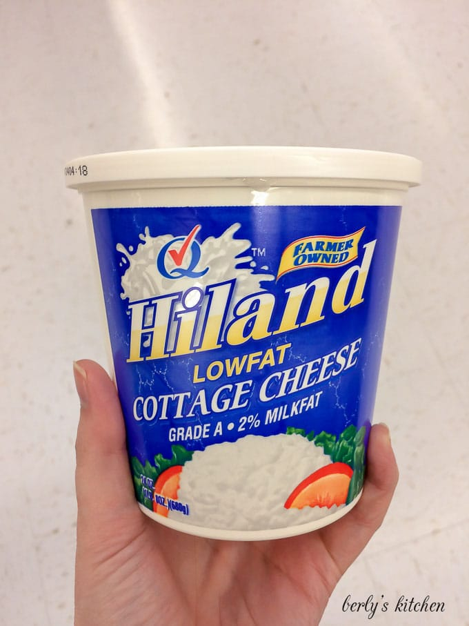 My hand holding a package of Hiland Dairy low fat cottage cheese.