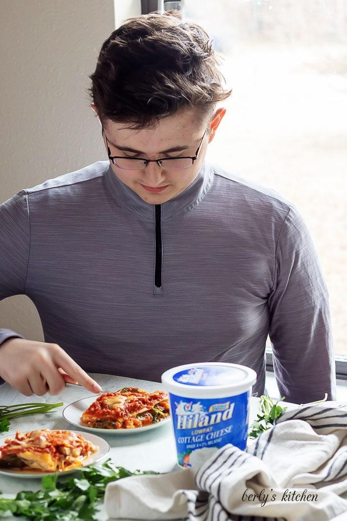 My son, at the kitchen table, enjoying the mushroom lasagna.