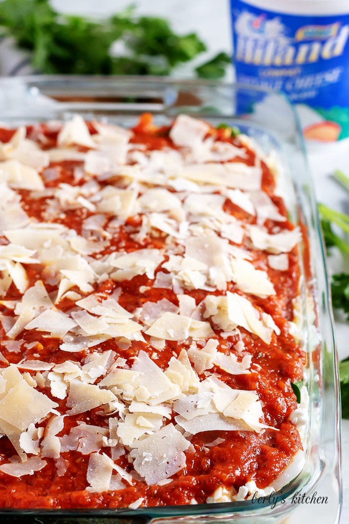 The final layer of marinara and shaved Parmesan cheese, just before baking.