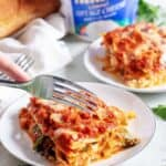 A slice of mushroom lasagna being cut with a fork.