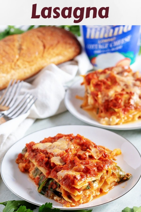 Two slices of mushroom lasagna, served with a loaf of wheat bread.