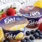 Two unopened packs of Oikos yogurt, surrounded by fresh fruit.