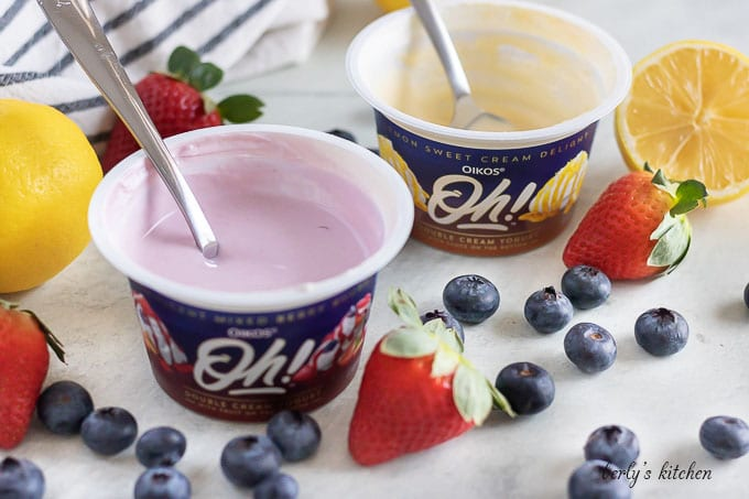 Two open containers of yogurt with spoons, surrounded by fresh fruit..