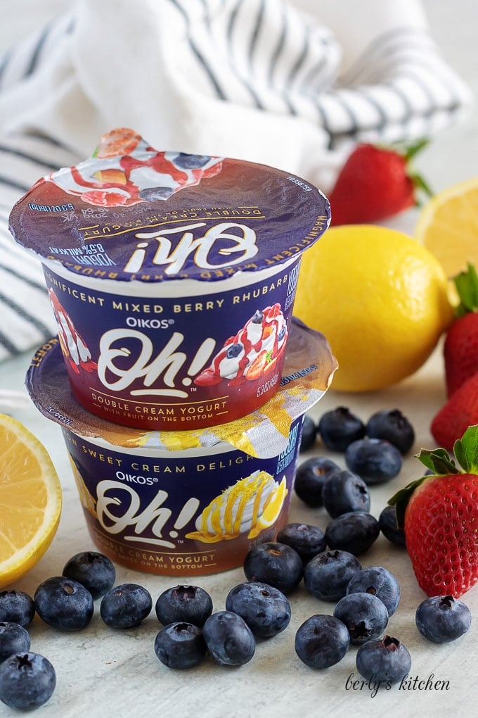 Stacked packs of mixed berry and lemon yogurts with fruit.