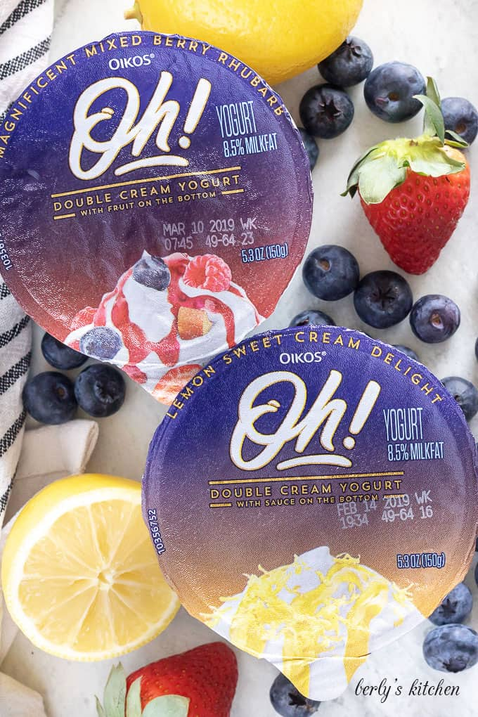 Top-down shot of the unopened lemon and mix berry yogurts.