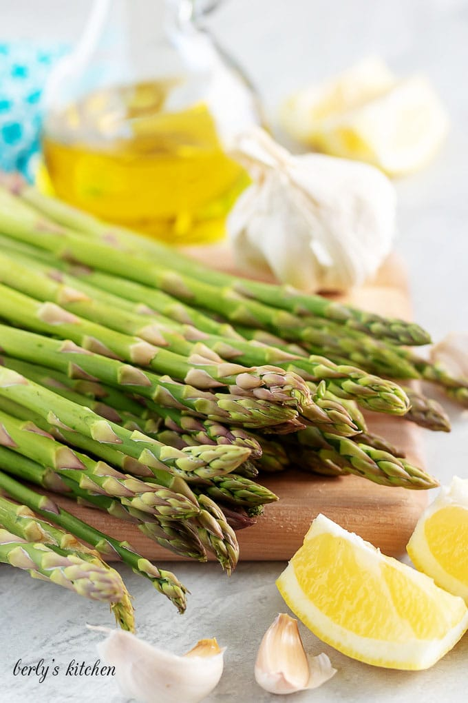 The side dish ingredients like asparagus, garlic, lemon juice, and oil.