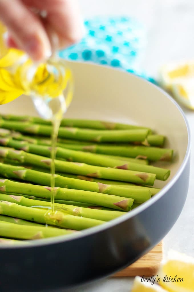 Olive oil being poured over asparagus, in the saute pan.