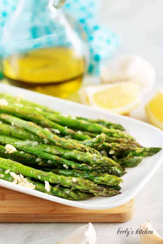Finished asparagus, covered in garlic, served on a rectangular plate.