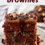 Three turtle brownies covered in caramel and stacked on a white saucer.