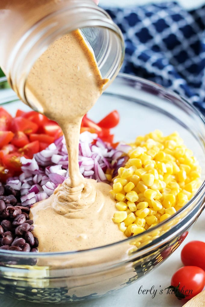 The southwest dressing being poured over the beans, corn, and other ingredients.