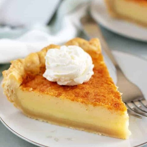 A large piece of buttermilk pie topped with whipped cream.
