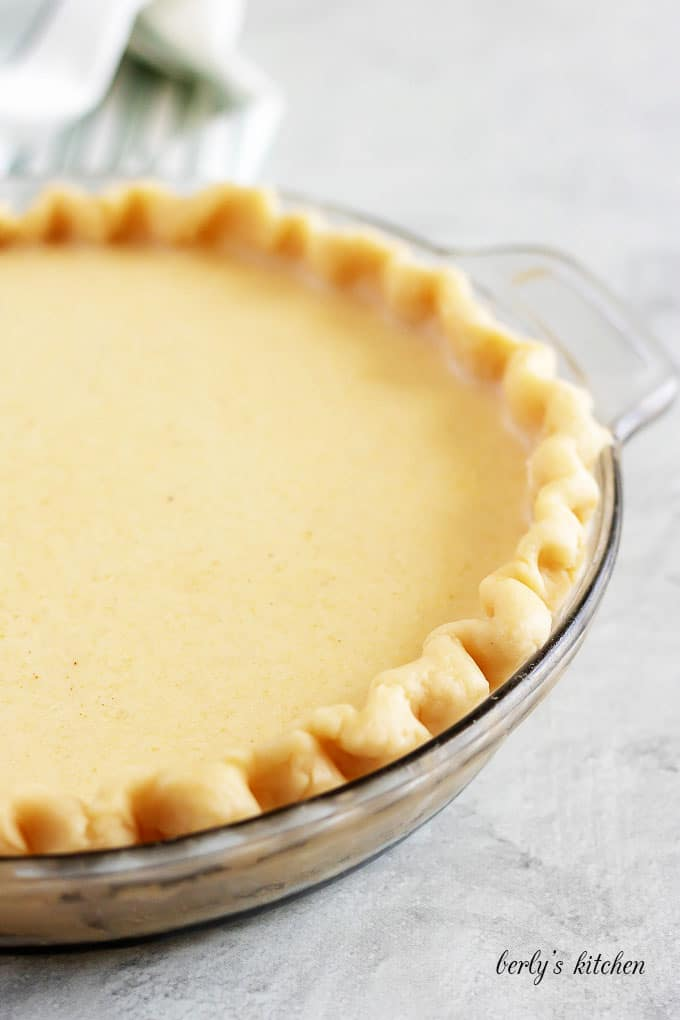 The buttermilk pie filling has been poured into the unbaked crust.