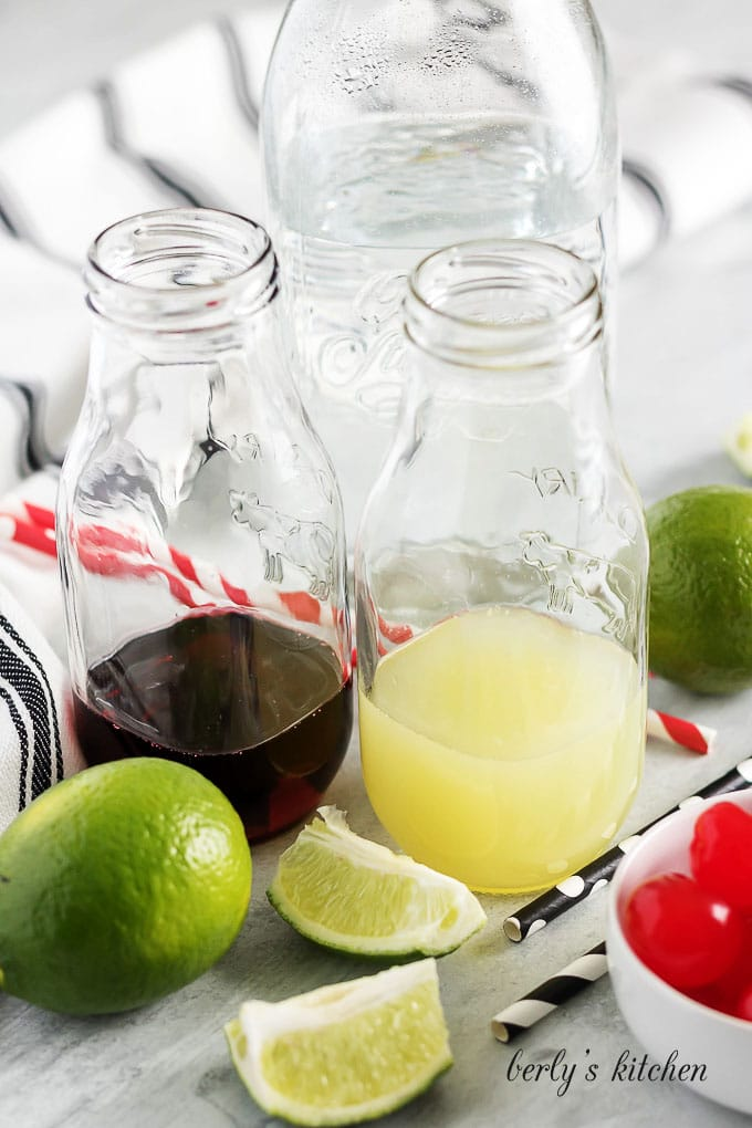 The cherry syrup and lime juice in small glass bottles.