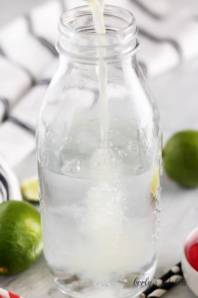 The lime soda has been prepped in a tall jar.