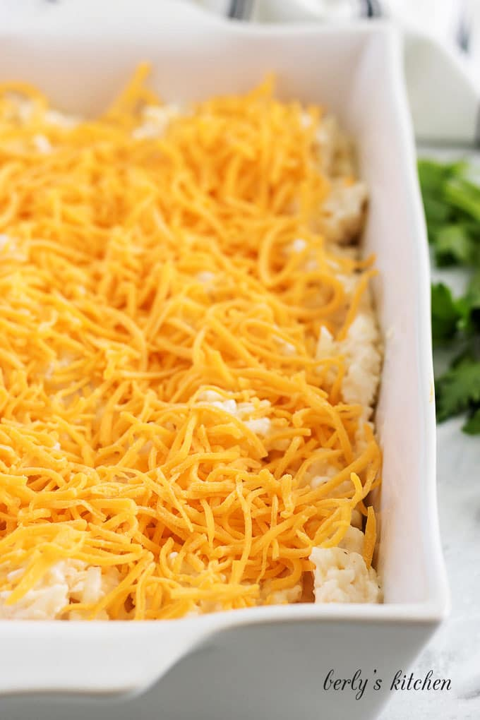 The unbaked casserole mixture, topped with cheddar, in a casserole dish.