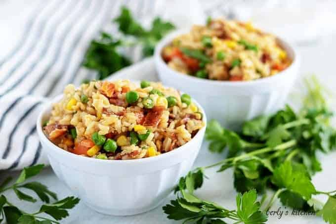 Two bowls of homemade fried rice garnished with fresh parsley.