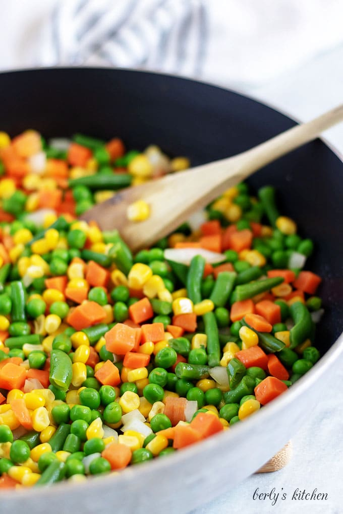 The frozen mixed vegetables, cooking in a large saute pan.