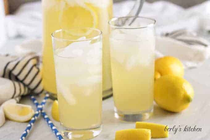 A pitcher and two glasses filled with ice and Instant Pot lemonade.