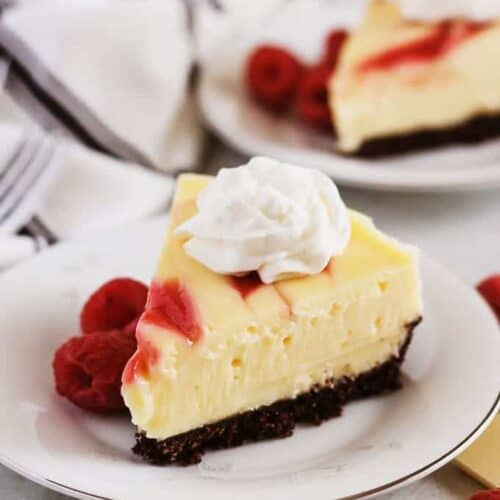 Slices of Instant Pot White Chocolate Raspberry Cheesecake topped with whipped cream.