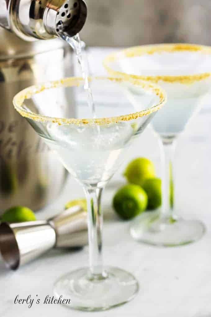 The key lime martini mixture being poured into the prepped glass.