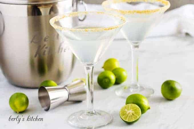 Two key lime martini cocktails rimmed with graham cracker crumbs.