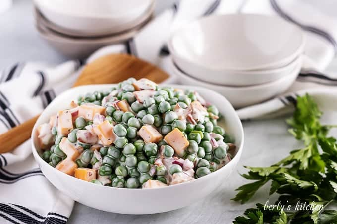 The pea salad served in a large bowl with a wooden spoon.