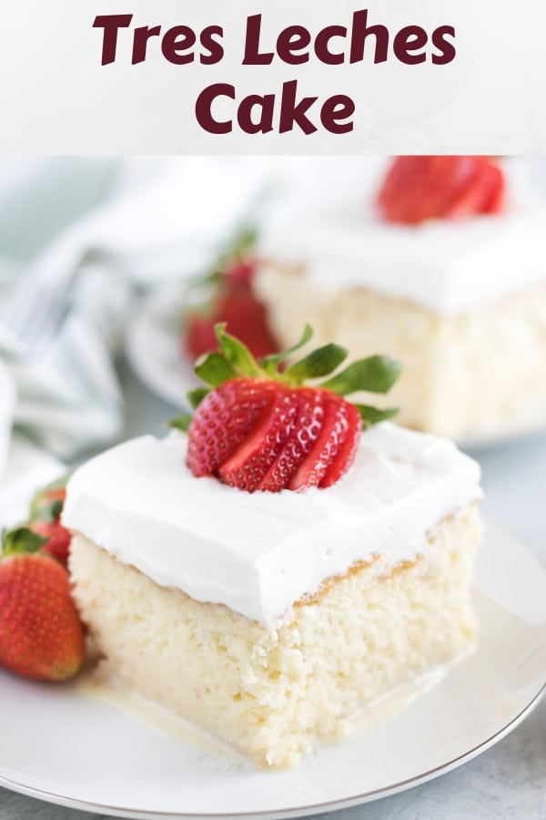 A piece of tres leches cake garnished with a strawberry.