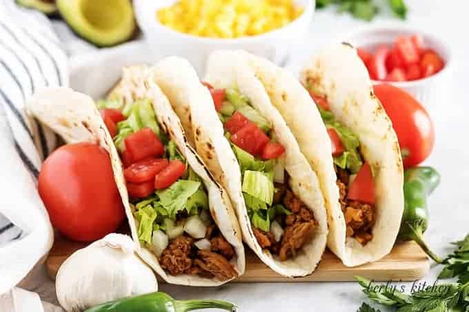 Three turkey tacos topped with shredded lettuce and diced tomatoes.