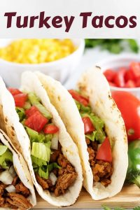 A close-up shot of the turkey tacos surrounded by fresh tomatoes.