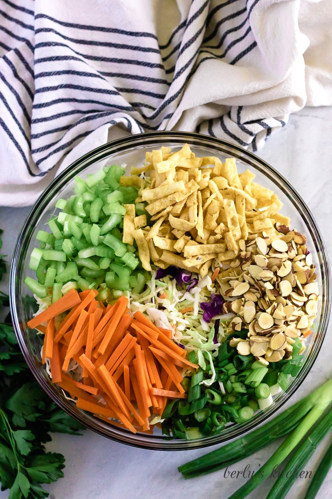 The cabbage, carrots, onions, and almonds in a mixing bowl.