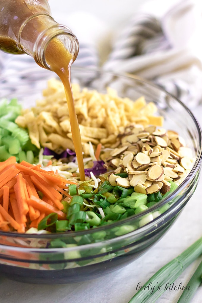 The dressing being poured over the cabbage and other ingredients.