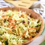 The finished Asian salad served in a large decorative wooden bowl.