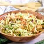 The Asian salad served in a wooden bowl, tossed with dressing.
