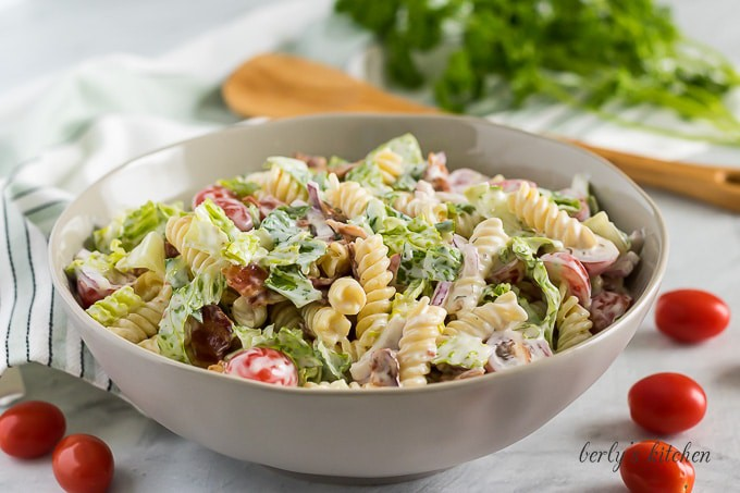 A bowl filled with the BLT pasta salad surrounded by grape tomatoes.