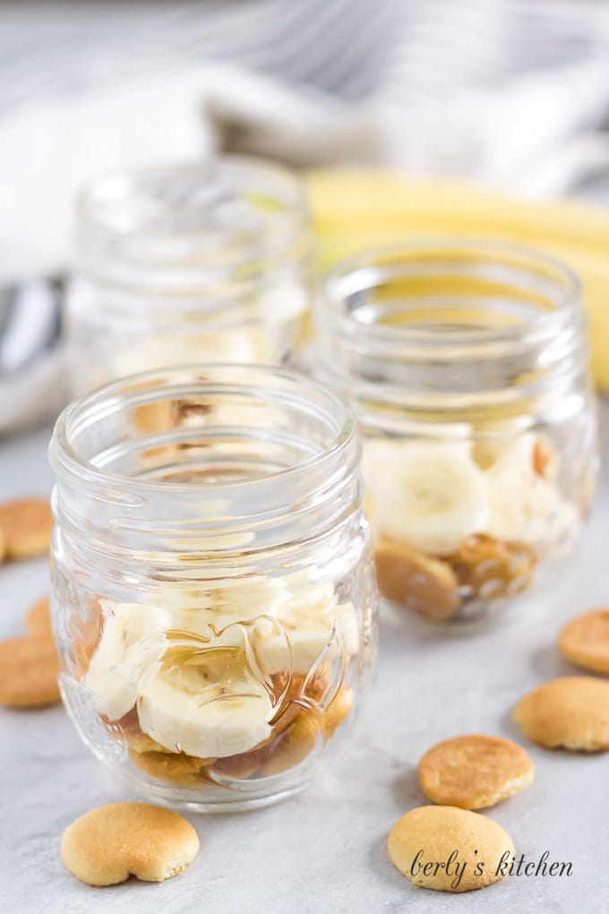Vanilla wafers and sliced bananas in the bottom of a mason jar.