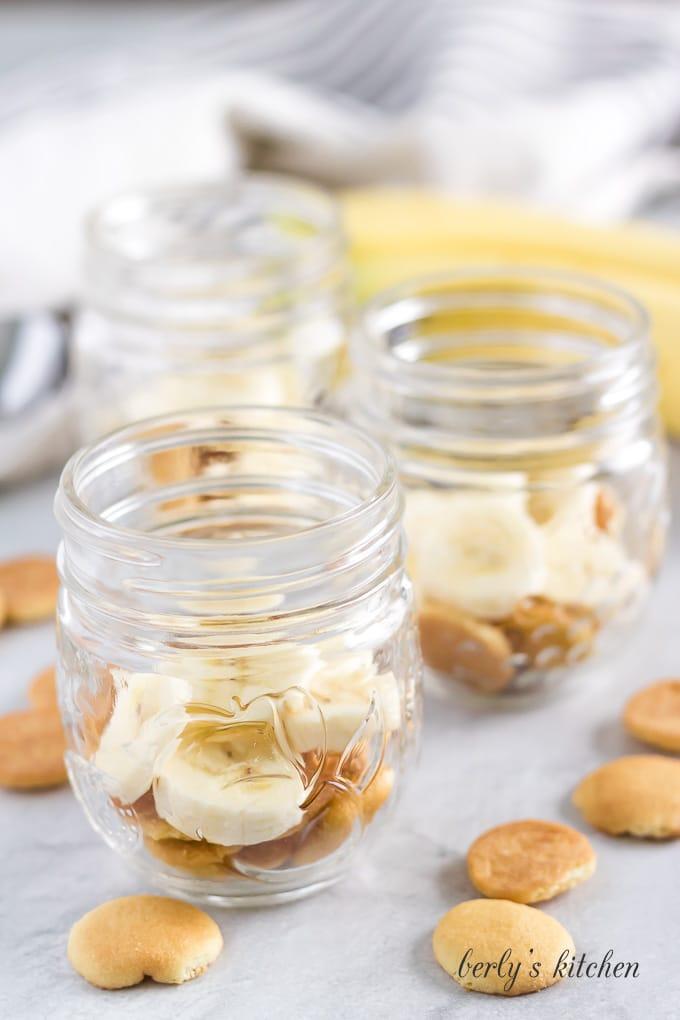 Vanilla wafers and sliced bananas in the bottom of a mason jar.