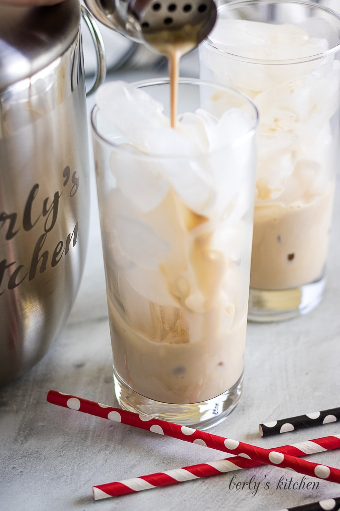 The irish cream being poured into a glass filled with ice.