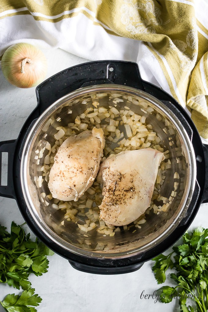 Aerial view of the chicken breast browning in the pressure cooker.