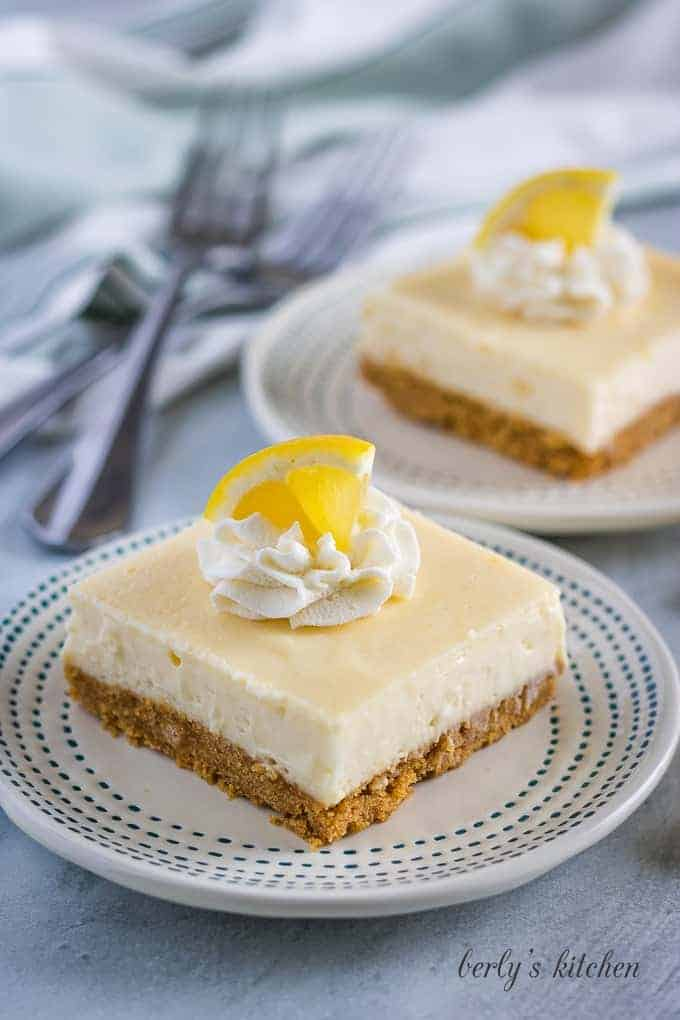 The lemon cheesecake bars garnished with whipped cream, and lemon wedges.