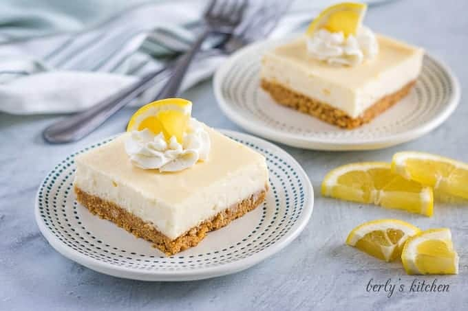 Two squares of the lemon cheesecake bars served on decorative plates.