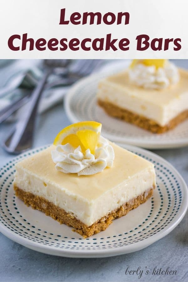 Two lemon cheesecake bars garnished with whipped cream and lemon wedges.