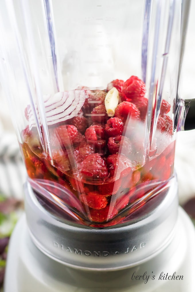 Raspberries, olive oil, and other ingredients in a blender to be combined.