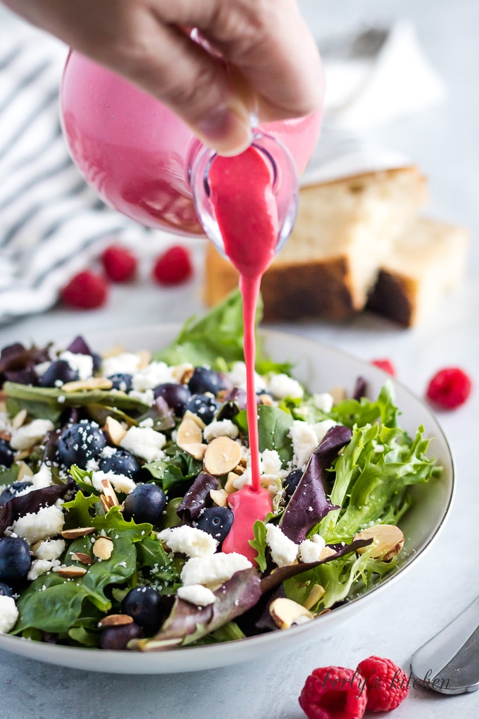 The raspberry vinaigrette being drizzled over a fresh Spring mix salad.