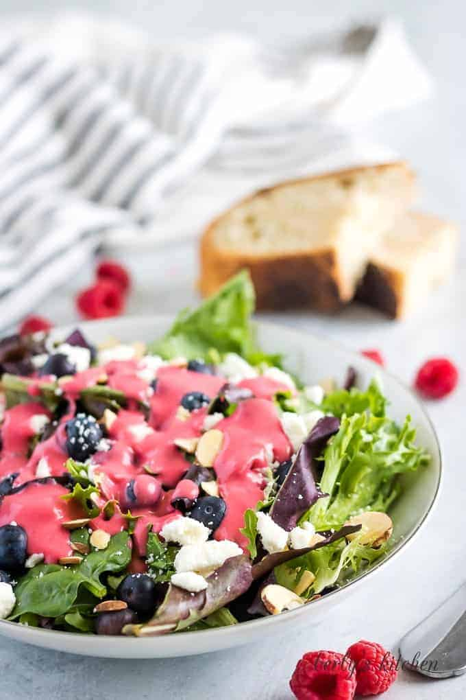 The salad dressing over a of Spring mix topped with feta cheese.