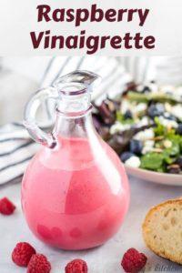 The bright homemade raspberry vinaigrette in a sealed dressing bottle.